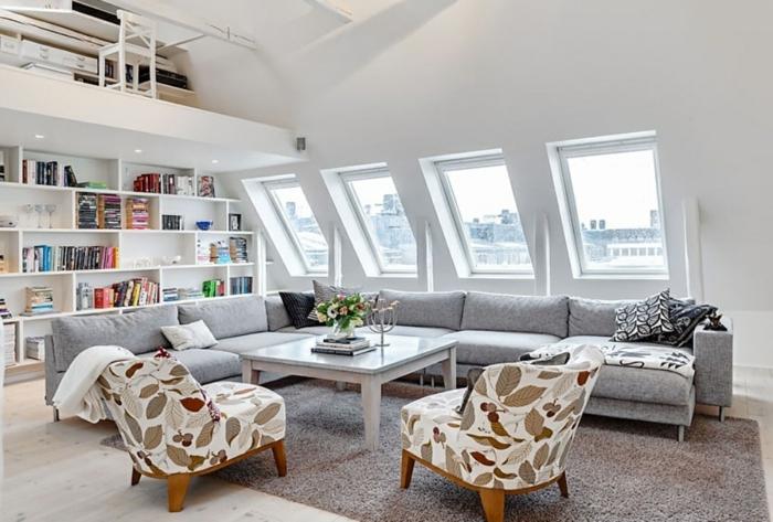 ideas sobre como decorar un salon comedor, sofá grande en gris y sillones con estampados de motivos botánicos, techo inclinado con ventanas