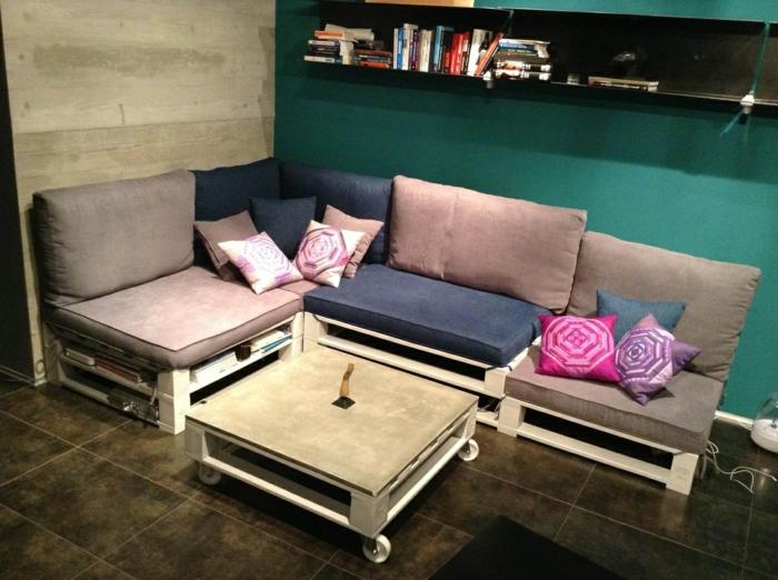 salón decorado de muebles con palets de madera, colchonetas en beige y azul y pared en verde saturado