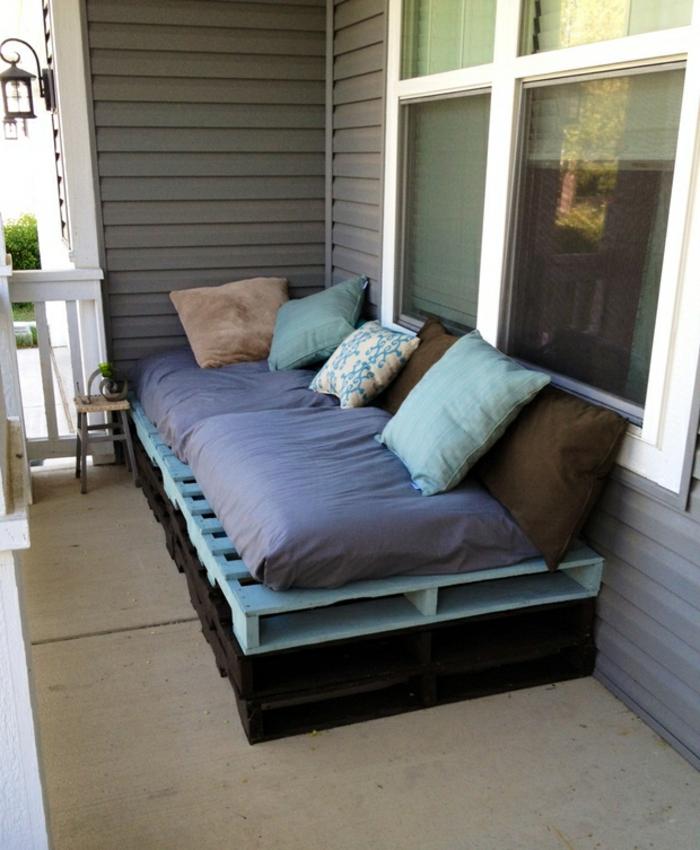 terraza de encanto con colchonetas en azul y pequeños cojines decorativos en azul y beige, ejemplos de cosas hechas con palets