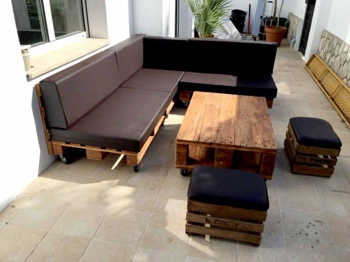 sofas hechos con palets de diseño, sofá tapizado de piel en color marrón, pequeños taburetes y mesa de palets