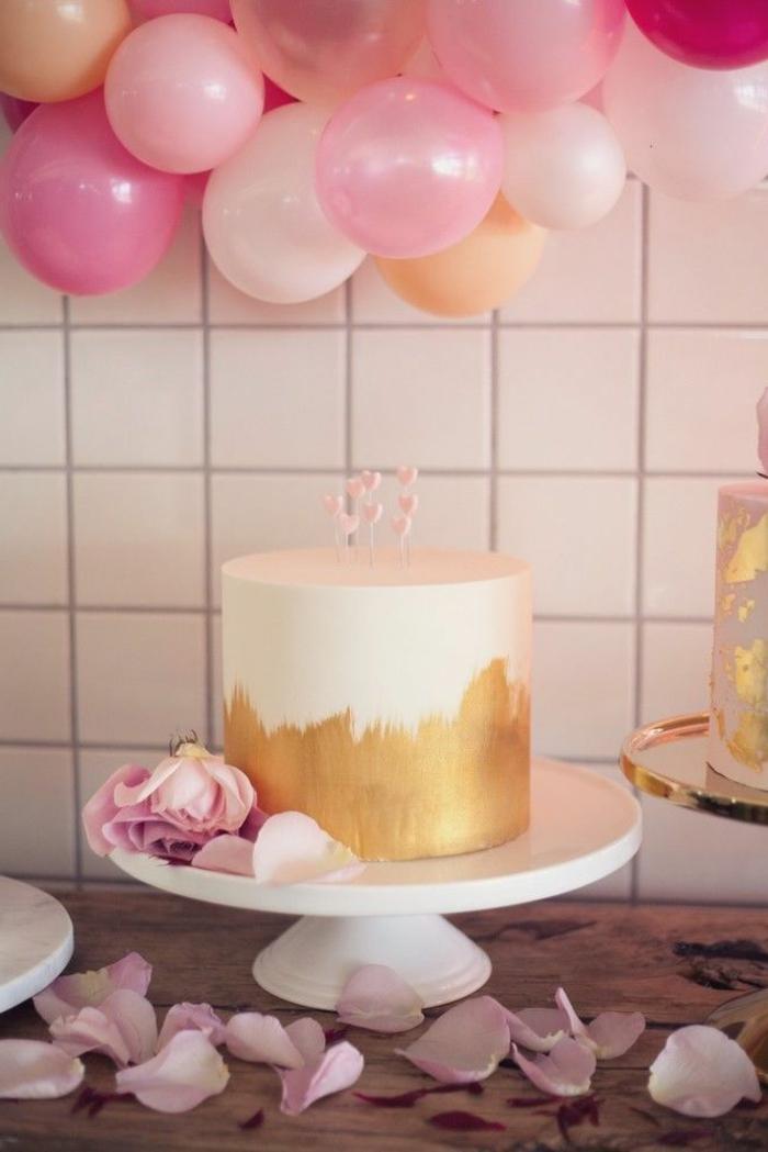decoracion fiesta cumpleaños, preciosa idea de decoración con balones en rosado, tarta sofisticada y pétalos de rosas