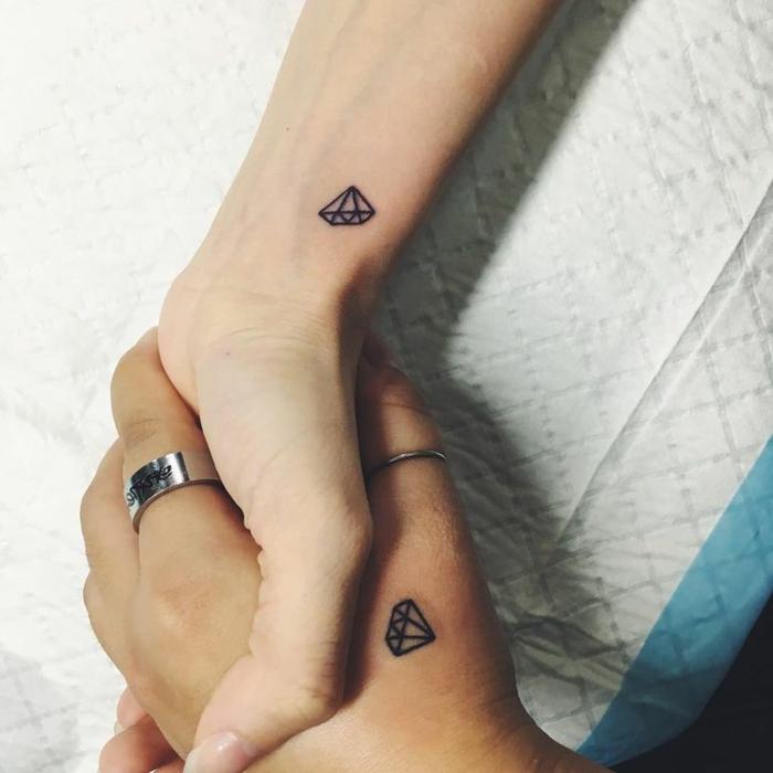 pequeños tatuajes antebrazo mujer en color negro, dos mujeres con tatuajes de pequeños diamantes en las manos