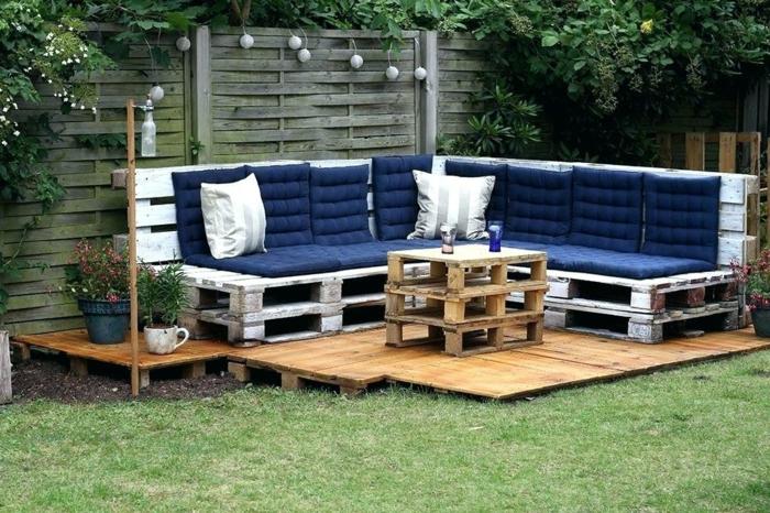 bonito jardín decorado de sofas hechos con palets, bancos de madera pintados en blanco con efecto desgastado y colchonetas en azul