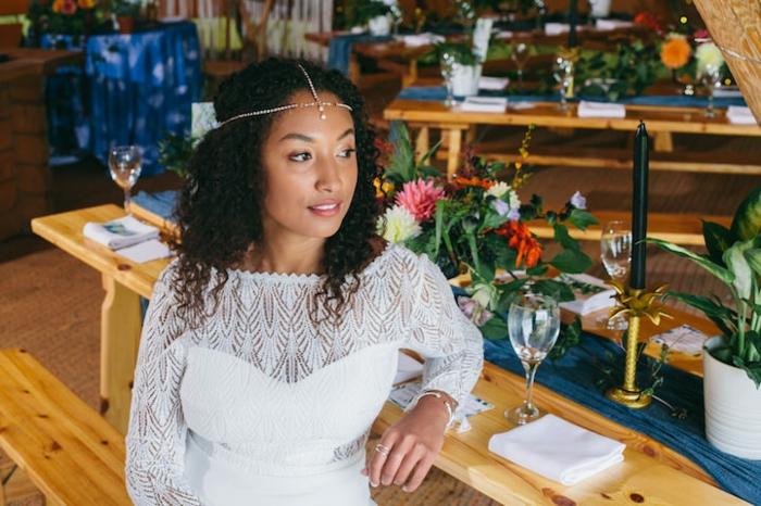 vestidos novia hippie de diseño sencillo, escote ilusión, vestido en color blanco nuclear, pelo suelto rizado con diadema