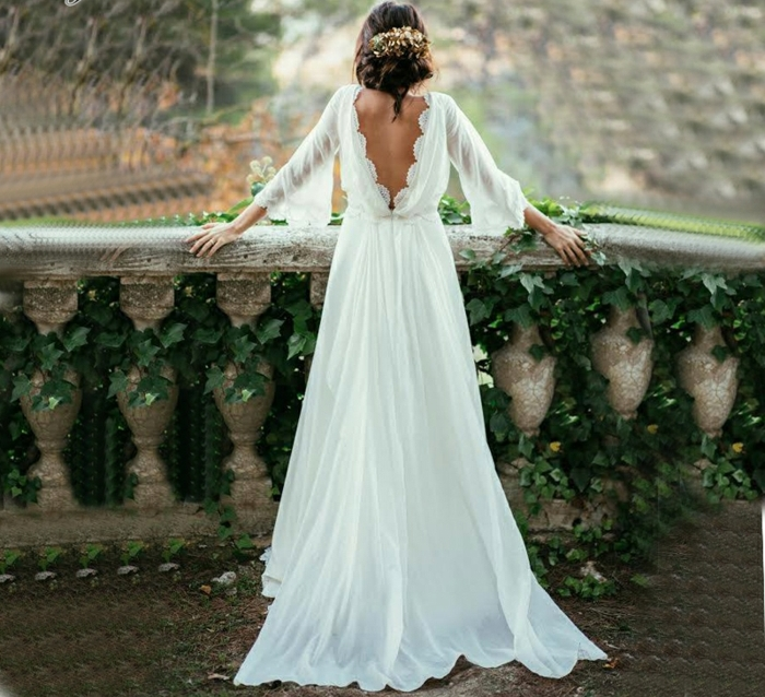 vestido largo con falda aireada, espalda descubierta y pelo recogido en grande moño, vestidos novia hippie en tendencia