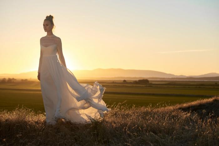 ejemplos de vestidos novia boho, vestido largo con falda aireada, parte superior con escote ilusión, pelo recogido en moño alto