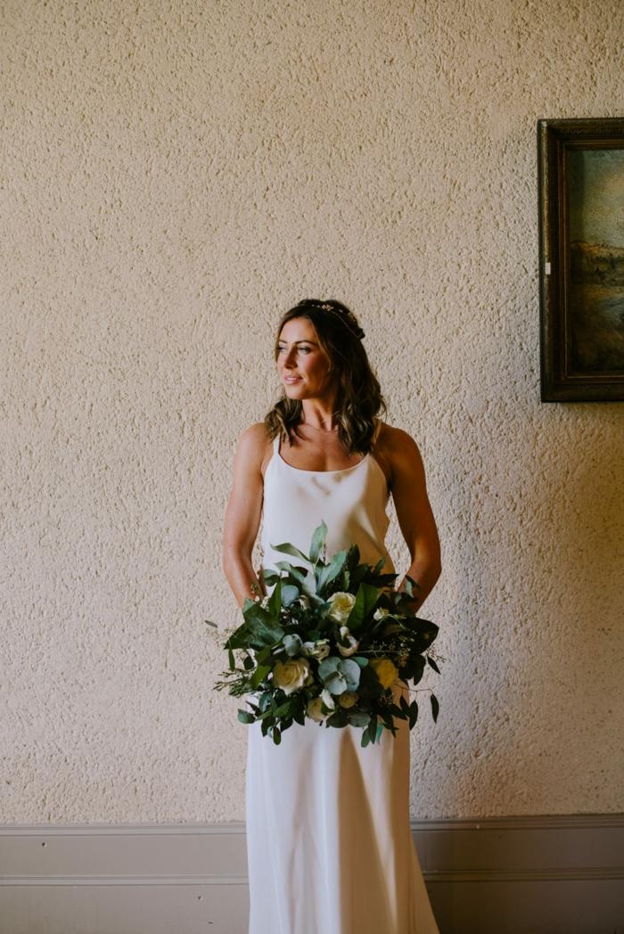 vestido boho de diseño sencillo y líneas rectas, parte superior sin mangas, pelo semirecogido decoración de flores