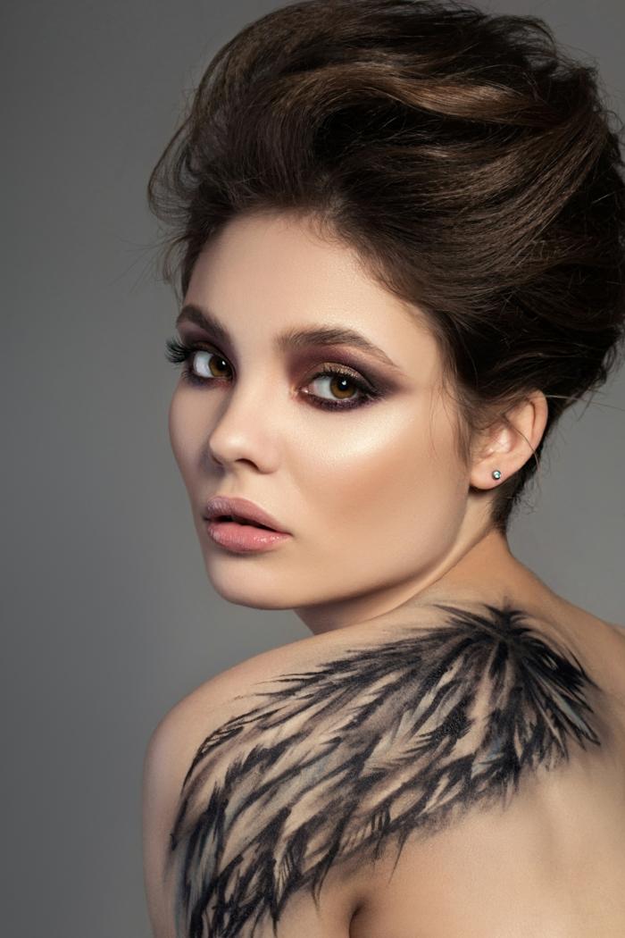 ideas bonitas con tatuajes de plumas, grande tatuaje de ala en la espalda, mujer con maquillaje fuerte y pelo recogido