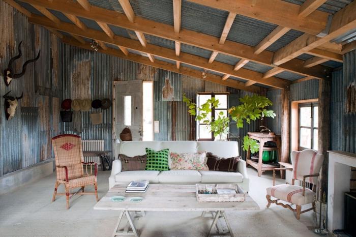 decoracion de salones rusticos, salon con techo inclinado con vigas de madera, paredes con efecto desgastado, sofa en blanco