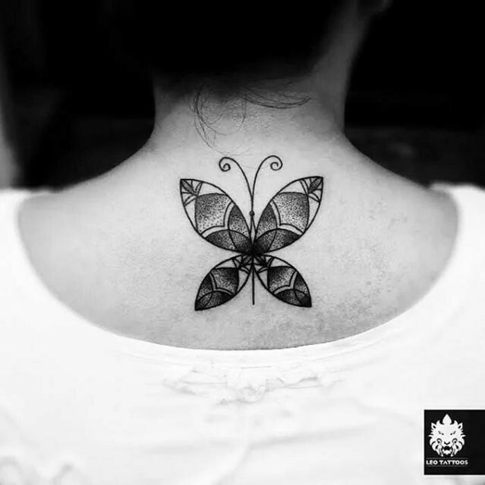 tatuajes de mujer con motivos geométricos, dibujo de mariposa con tinte negro tatuado en la parte superior de la espalda
