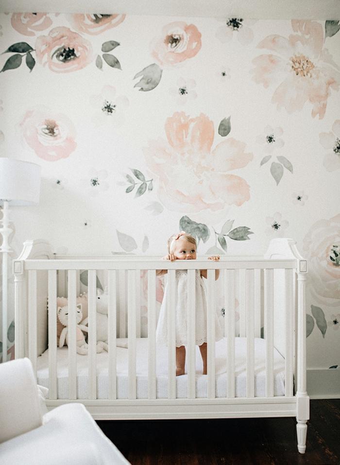 habitación decorada en colores pastel, paredes con papel pintado motivos florales, pequeña cama de madera en blanco