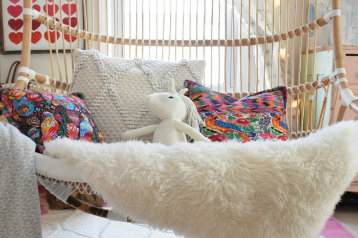 dormitorios de niñas con decoración original, cuña de mimbre colgante con cojines decorativos en colores y manta peluda en blanco