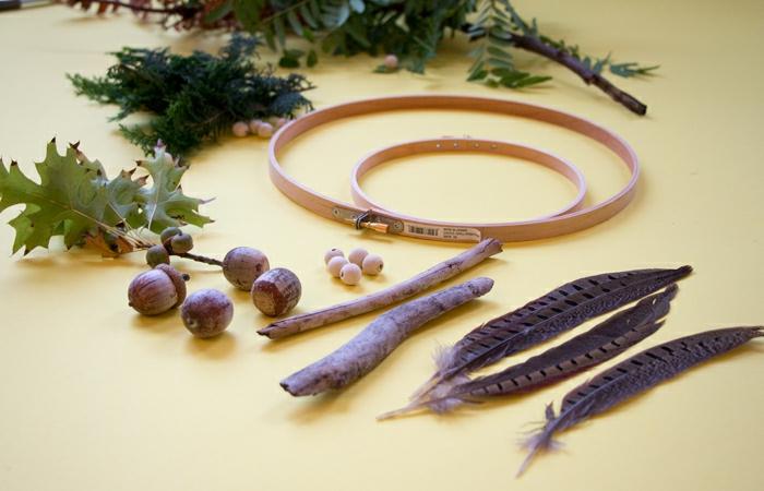materiales necesarios para hacer un atrapa sueños casero, aros de madera de diferente tamaño, plumas de halcón, palos de madera, hojas de árboles verdes
