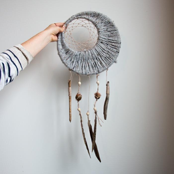 atrapasueños ganchillo original decorado de hilo en gris, palos de madera y plumas de halcón, manualidades para decorar la casa paso a paso