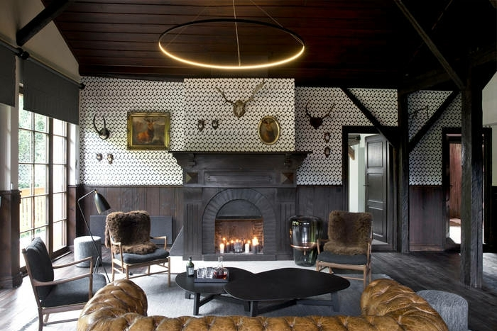 precioso salon decorado en colores oscuros, decoracion rustica y muebles de epoca, sofá tapizado en piel en marrón