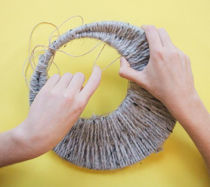 como hacer atrapasueños manualidades paso a paso, dos aros de diferentes tamaño envueltos de hilo en beige