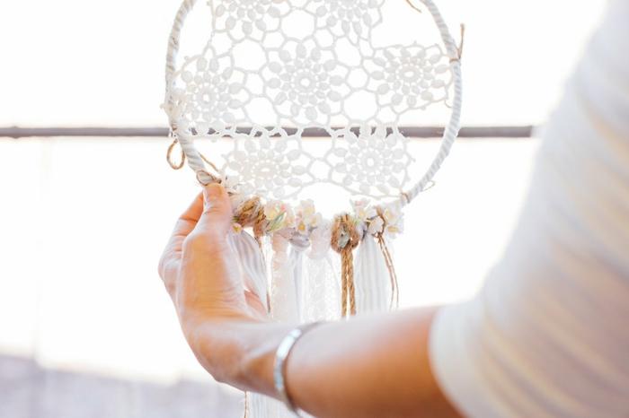 bonito atrapasueños de crochet en estilo bohemio, aro de madera con flroes en ganchillo y cintas de telas