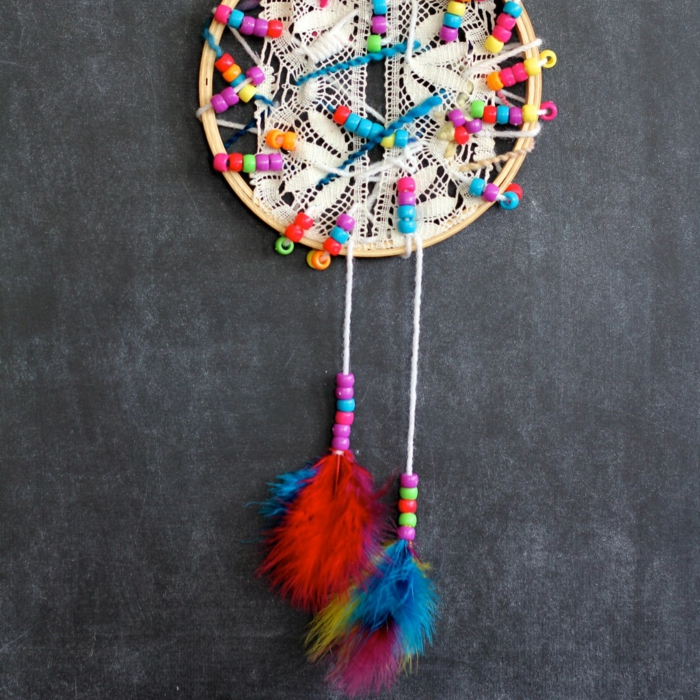 atrapasueños manualidades de encanto, aro de madera con trozos de encaje y cuentas coloridas, pompones en rojo, azul y amarillo