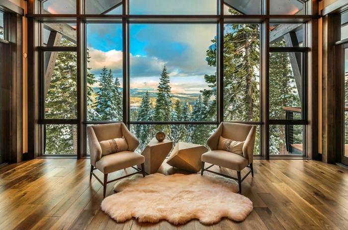 salon moderno con grandes ventanales y bonita vista, sillones de diseño y alfombra peluda en blanco, tendencias salones rústicos