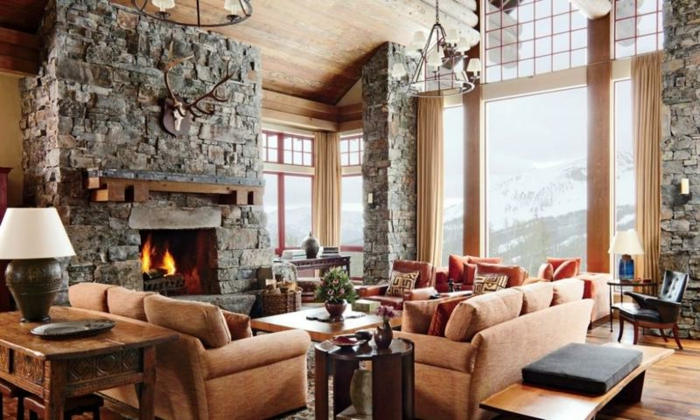 decoracion de salones modernos con chimenea en colores cálidos, paredes de piedra y grandes ventanales