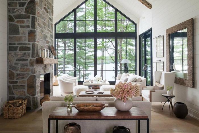 grande salón decorado en blanco con elementos de piedra y madera, muebles modernos de diseño