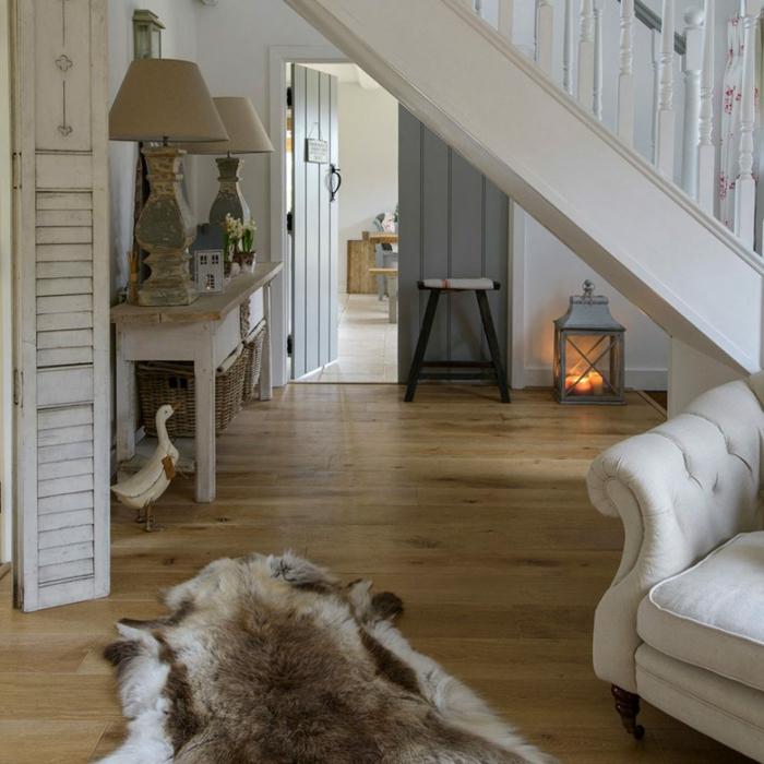 ideas de decoracion salones modernos con chimenea, salon con parquet decorado en blanco y gris y alfombra de piel