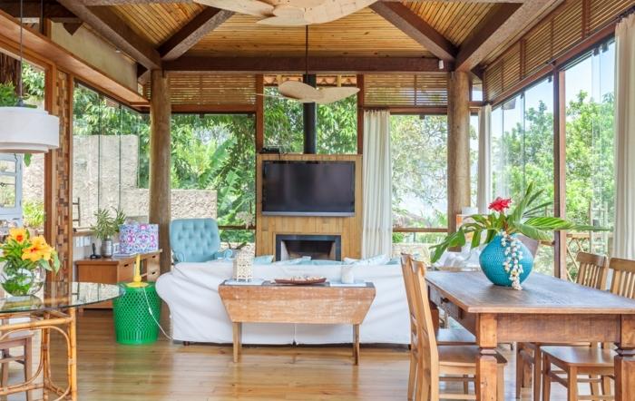 bonito salon decorado en tonos claros con grandes ventanales, techo y suelo de madera, decoración de flores, ideas de salones modernos con chimenea