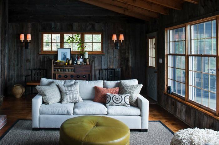 salon oscuro decorado en colores terrosos con un sofá en color marfil, salones rústicos de encanto