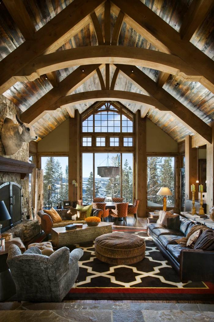 fotos de salones rusticos modernos, grande salon abuhardillado con techo con vigas, alfombra en ornamentos geometricos y muebles tapizados en piel
