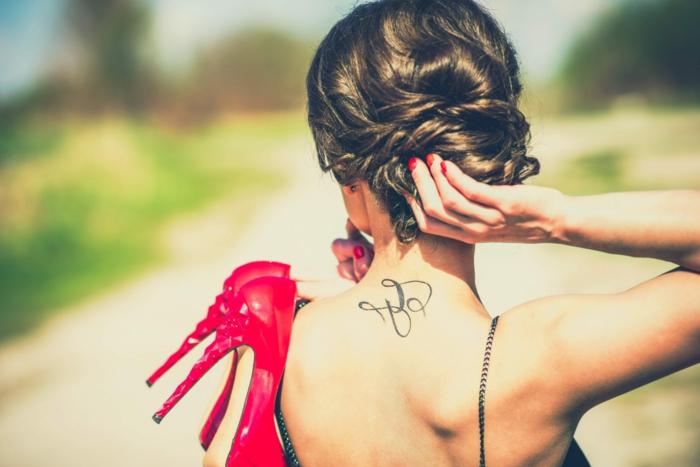 bonitos detalles para tatuarse en la nuca, tatuajes nuca mujer, mujer con pelo recogido en moño bajo y espalda descubierta