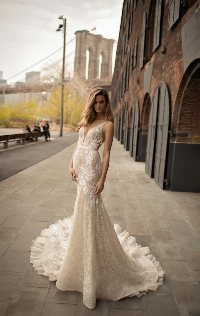 vestido novia romantico corte sirena con larga cola adornado de encaje, escote grande y pelo suelto ondulado