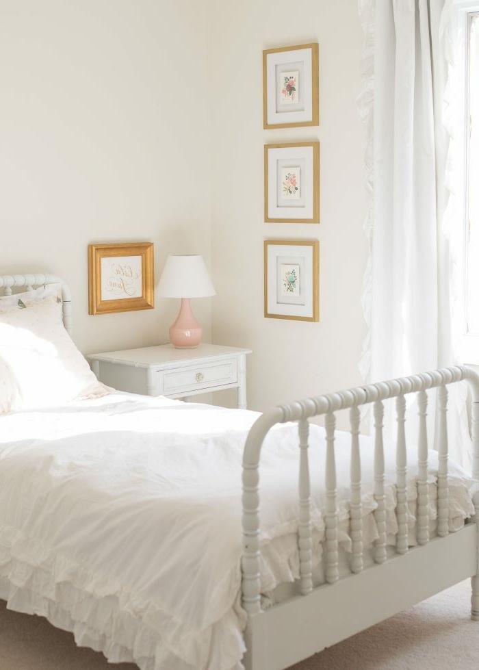 habitación decorada en blanco con cuadros decorativos en la pared, cama en estilo vintage ne blanco, decoración habitaciones de niñas
