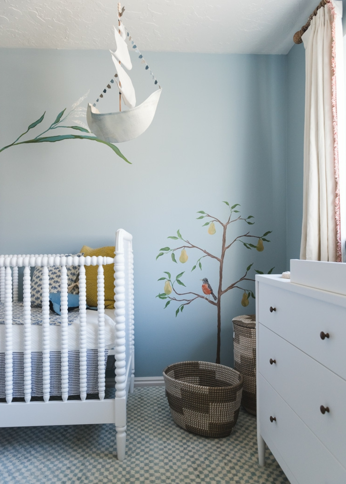 precioso ejemplo de cuartos de niñas modernas, cama de bebe en blanco, paredes en azul con dibujos