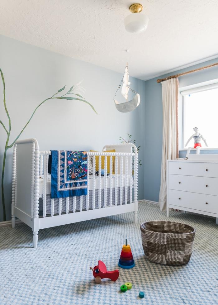 ambiente de encanto decorado en azul celeste, cama de bebé de madera pintada en blanco, suelo con moqueta en cuartos en blanco y azul