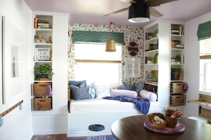 bonita habitación con partes de pared en papel pintado con motivos florales, cama cómoda con cojines decorativos