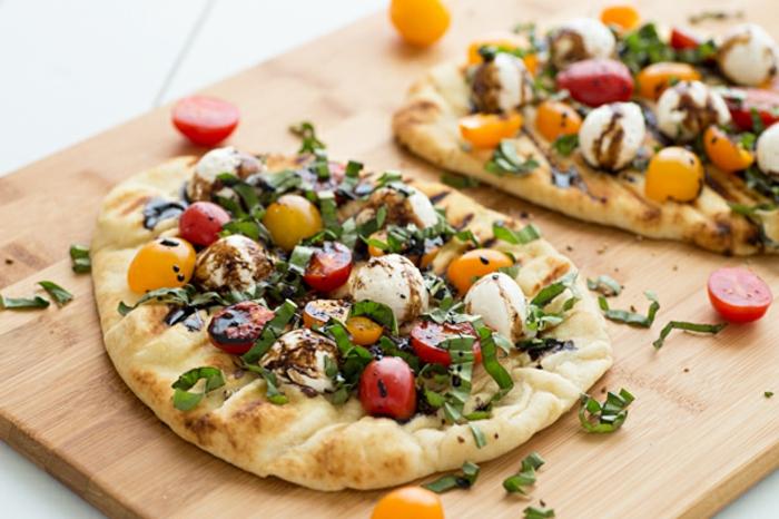 pequeñas pizzas casera, pan árabe con tomates cherry amarillos y rojos, cebollín y mozarella