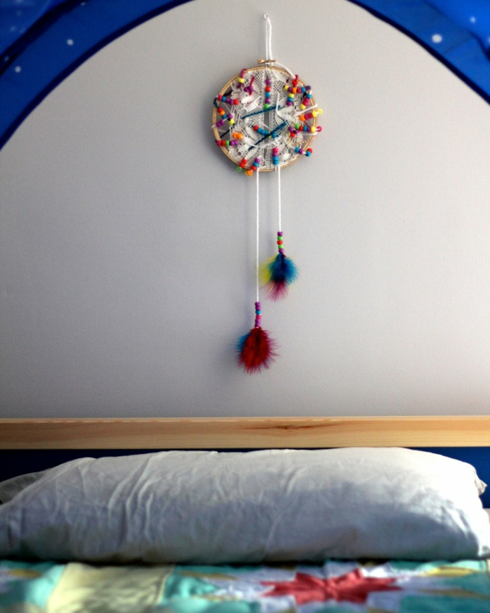 pequeños atrapasueños colorido con pompones colgado sobre la cama, manualidades decoracion originales