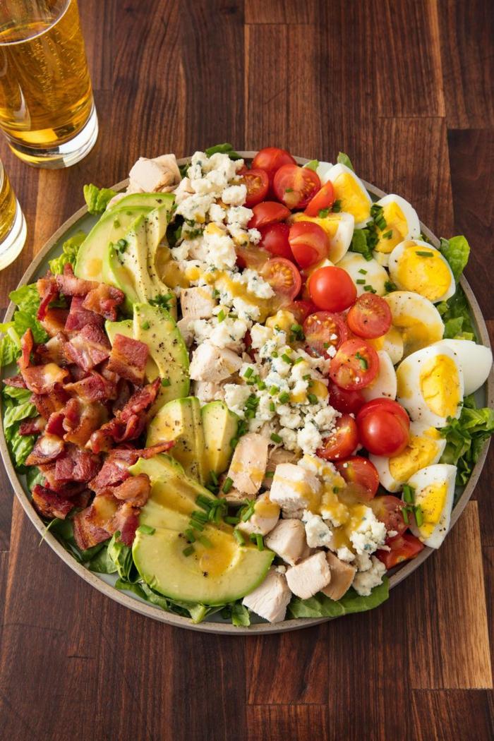 grande ensalada con tocino, aguacate, trozos de pollo, queso, tomates cherry y huevos cocidos