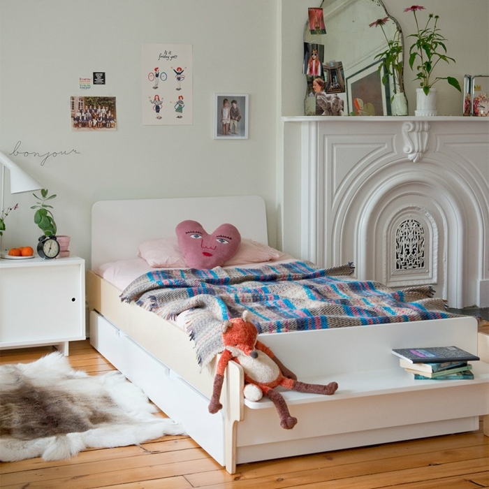 cuarto de niñas de diseño, dormitorio en blanco con cama individual adornada de peluches y cojines decorativos, suelo de parquet con alfombra vaca