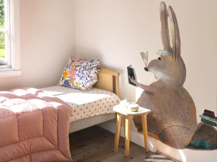 decoracion dormitorios de niñas, paredes en color pastel, cama individual de madera y vinilo de pared con dibujo de conejo
