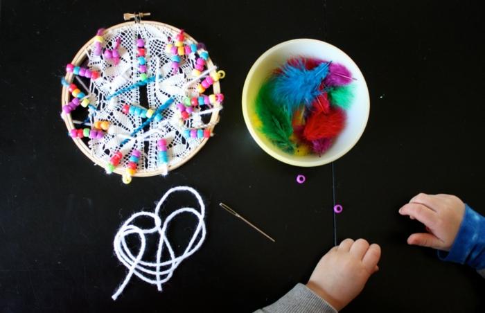 ideas creativas de manualidades para niños, hilo blanco, aguja, aro de madera de crochet, plumas artificiales coloridas