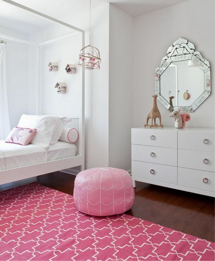 habitacion niñas en blanco con elementos en rosado, alfombra ornamentada y taburete de piel