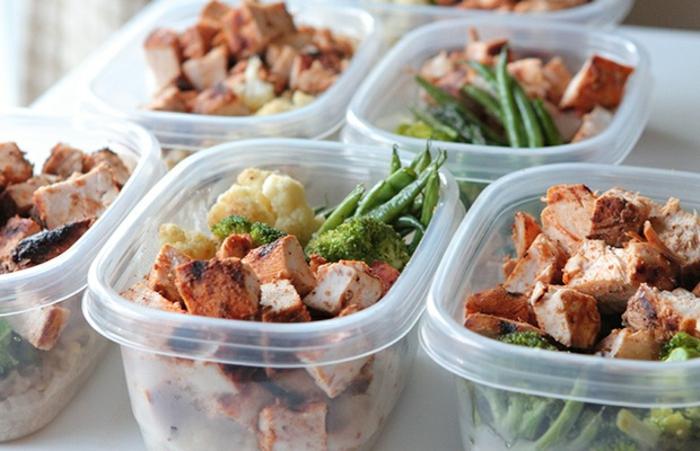 cajas con almuerzo saludable, trozos de carne de cerdo, floretes de brócoli y colioflor y espárragos