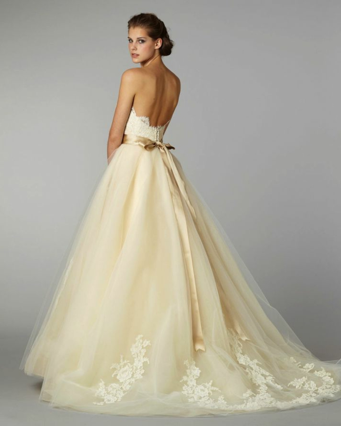 precioso vestido en color marfil con falda amplia adornada de apliques de flores, cinta en dorado y espalda descubierta