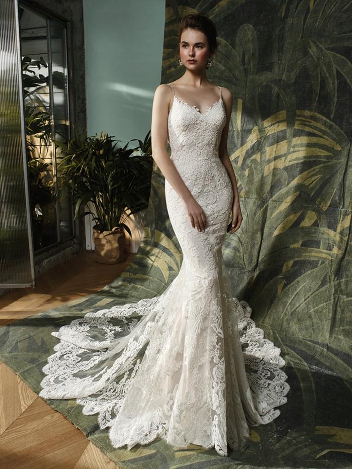 vestido romantico en blanco perla con larga cola de encaje, escote redondo y correas muy final, pelo recogido en moño