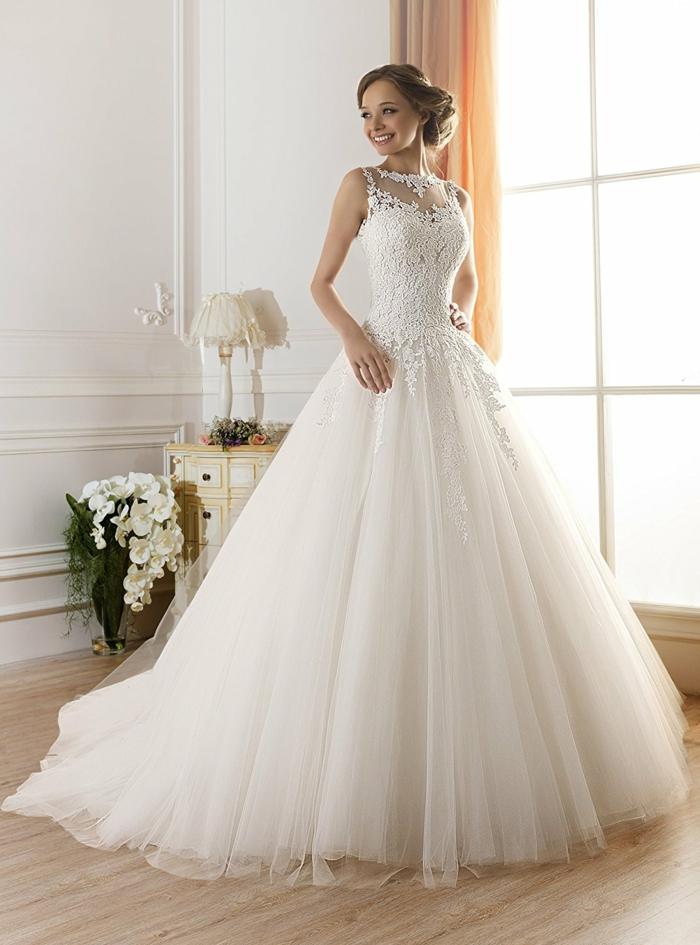 vestido corte princesa con falda muy amplia y parte superior de encaje con escote ilusión, pelo recogido en moño bajo