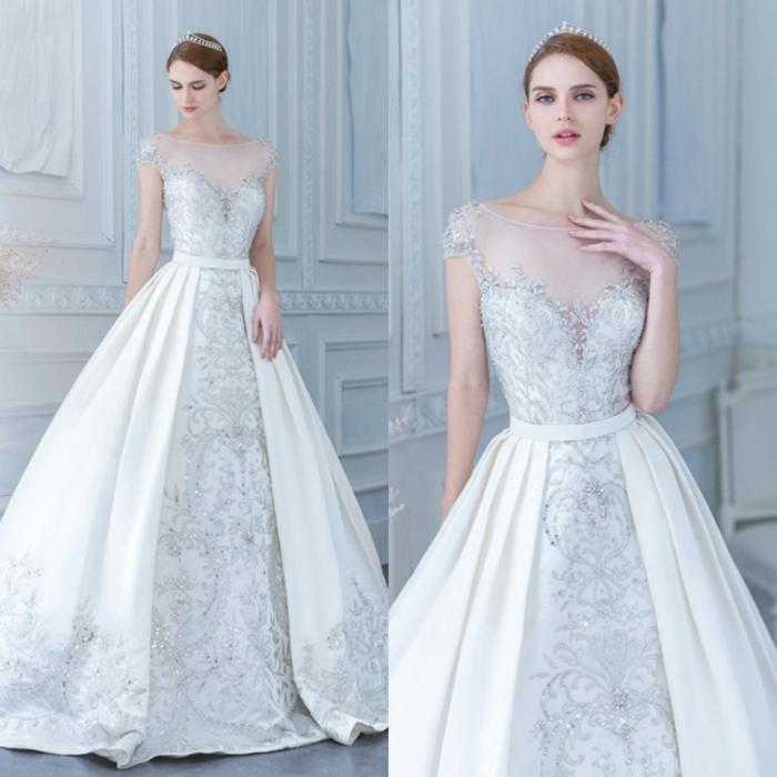 vestido de novia romántico tipo princesa con larga falda, encaje con brillo, motivos florales y escote ilusión