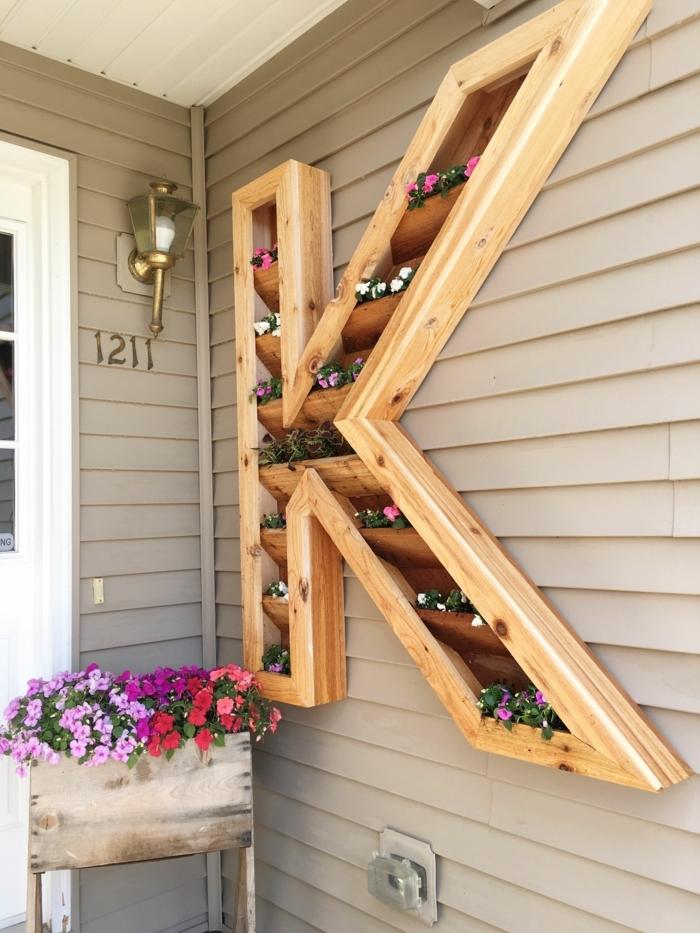 jardineras con palets para decorar la veranda o el jardín, jardinera colgante en forma de la letra K con flores pequeñas