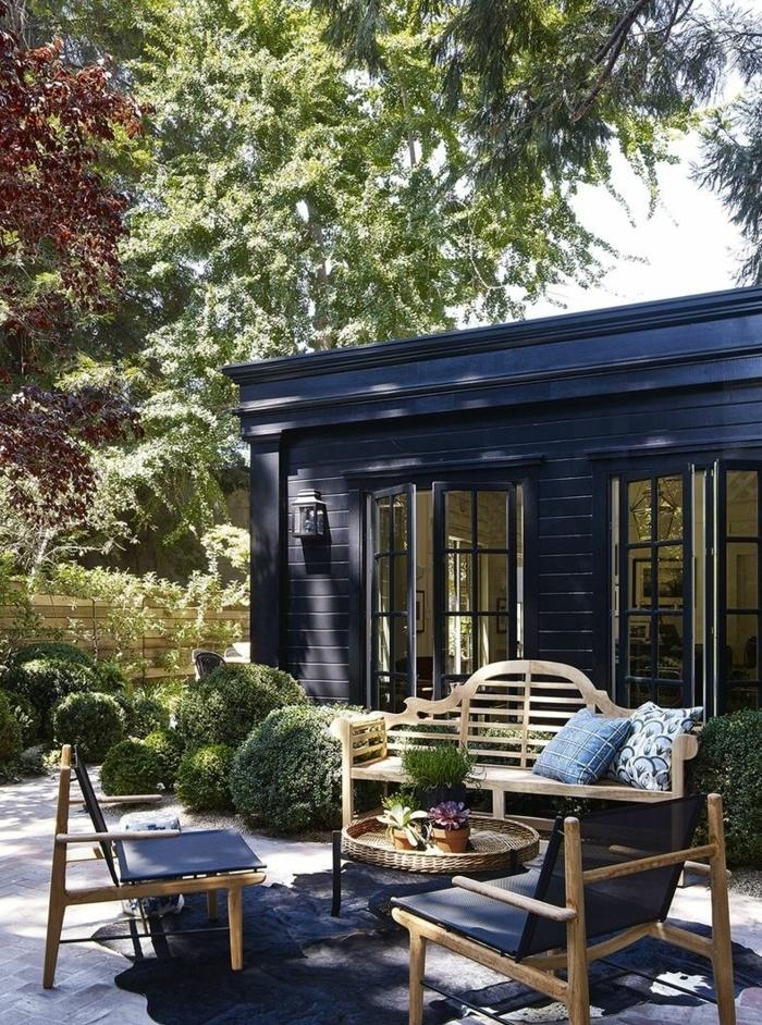 decoracion terrazas ideas y consejos, bonito patio con muebles de madera y decoración en tonos oscuros