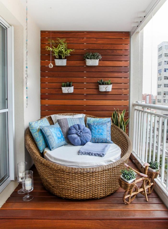 decoracion terrazas pequeñas ideas originales, grande sillon de rattan con muchos cojines decoratiovs y jardinera vertical
